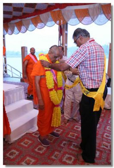 A disciple garlands Acharya Swamishree Maharaj on behalf of all the other disciples