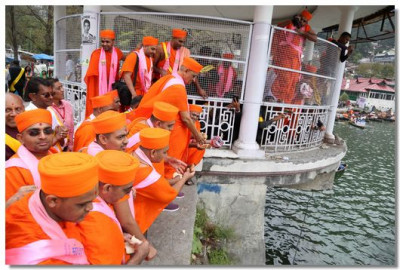 Acharya Swamishree Maharaj gives prasad to the fishes in Lake Nainital