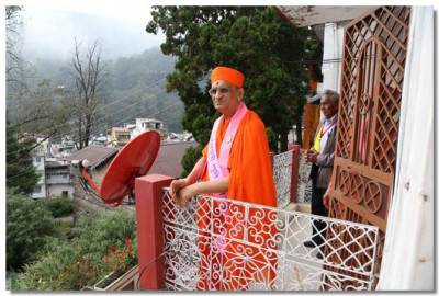 Acharya Swamishree Maharaj on the balcony of the house