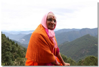 Acharya Swamishree Maharaj gives darshan in front of the Himalayan range of mountains