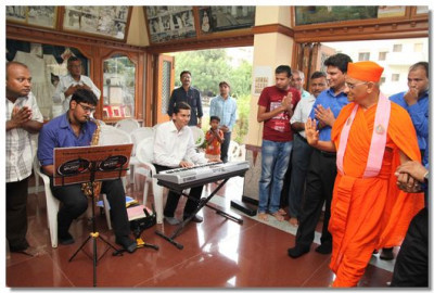 Acharya Swamishree is greeted by students of the school playing tunes