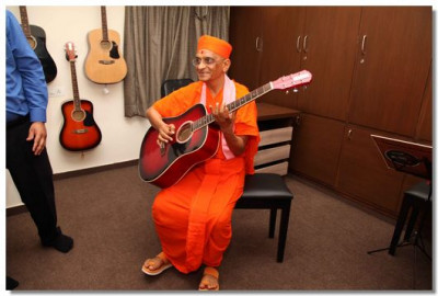 Acharya Swamishre plays a tune on the guitar