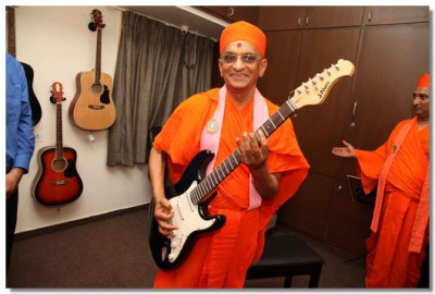 Acharya Swamishree with an electric guitar