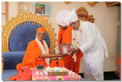 Shree Nitinbhai is honoured with a prasad paag by Acharya Swamishree for his continued assistance to the sanstha