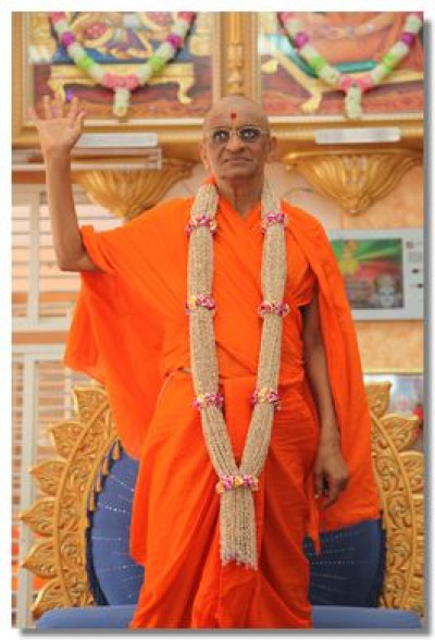 Divine darshan of Acharya Swamishree with a garland made with 75,000 beads of juar by ladies of Naranpar
