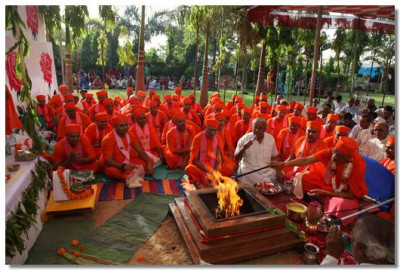 Acharya Swamishree puts ghee in the havan as the Lords prayers are recited