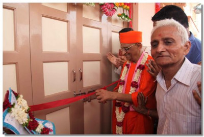 Acharya Swamishree cuts the ribbon to mark the opening of the temple