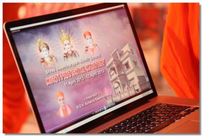 Acharya Swamishree views the mahotsav video title scene