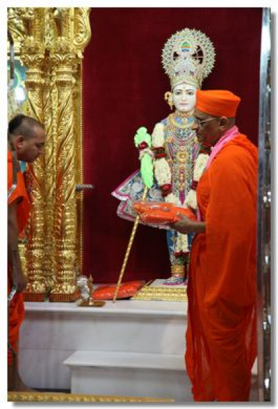 Acharya Swamishree Maharaj consecrates the new saffron robes to be worn by the new Sants