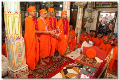Acharya Swamishree and the new sants peforms aarti to the Lord Swaminarayan