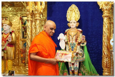 Acharya Swamishree with the latest edition of Shree Ghanshyam Vijay