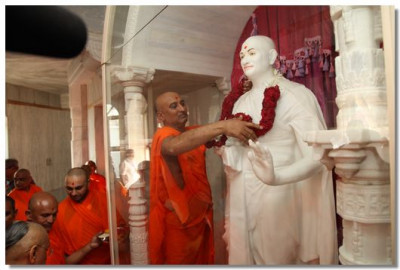 Sadguru Shree Bhagvatpriyadasji Swami puts a garland on the murti of Acharya Swamishree
