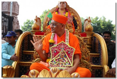 Acharya Swamishree showers His blessings during the procession