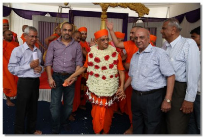 Acharya Swamishree with a vagha of flowers departs the sabha mandap