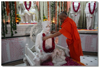 Acharya Swamishree puts a garland on Jeevanpran Swamibapa's murti on the first floor