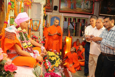 Disciples perform aarti to Acharya Swamishree