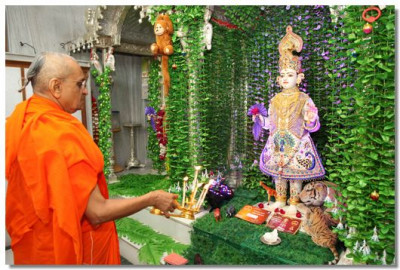 Acharya Swamishree performs aarti to Lord Swaminarayan.