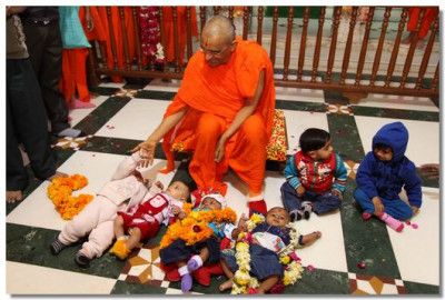 Acharya Swamishree blesses some of the young babies of Kadi