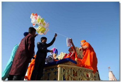 Acharya Swamishree releases balloons to mark the start of the procession