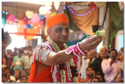 Acharya Swamishree offers the cake to Lord Swaminarayan