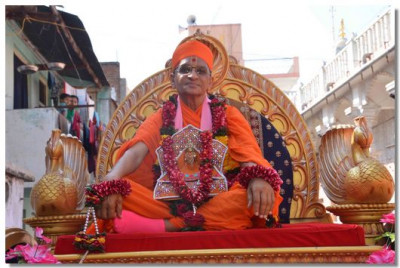 Acharya Swamishree gives darshan on a chariot during a procession