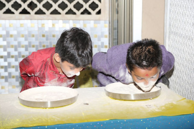 Young disciples try and find coins in the flour