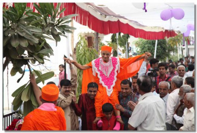 Acharya Swamishree being carried by disciples to the stage
