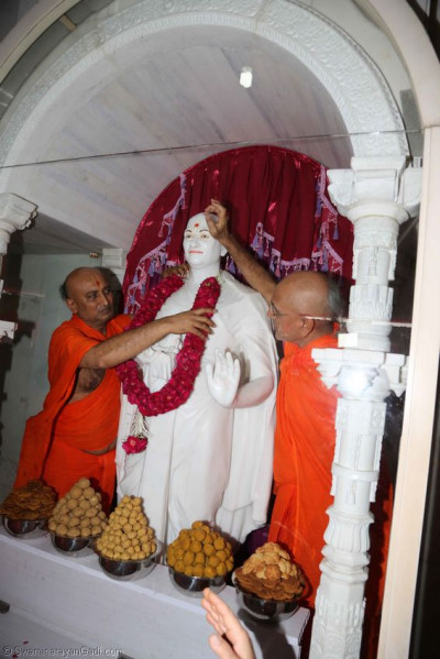 Sants put a garland and chandlo on the murti of Acharya Swamishree