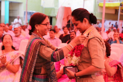 Dr Kanan Desai of the police force is honoured with a garland and shawl