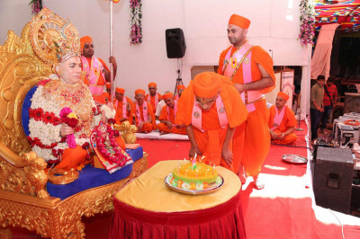 Acharya Swamishree Maharaj blows the candles on the cake