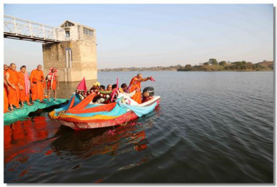 Acharya Swamishree places rose petals into the water