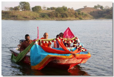 Acharya Swamishree drives the boat to the bank