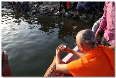 Acharya Swamishree places a diwo in the water
