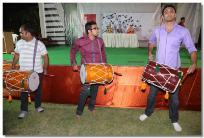 Dhol players perform as Acharya Swamishree arrives