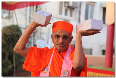 Acharya Swamishree holds up some of the bricks which will be used in the shilanyas ceremony