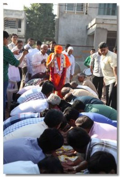 Acharya Swamishree arrives at the temple grounds welcomed by disciples with a path of hands