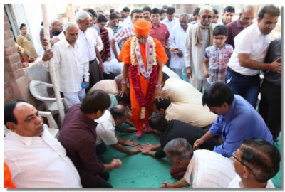 Disciples place their hands on the ground making a path for Acharya Swamishree to walk on