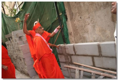 Acharya Swamishree views the exterior of the building