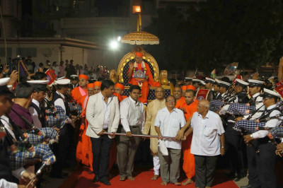 Disciples pull Acharya Swamishree Maharaj's chariot as the band plays