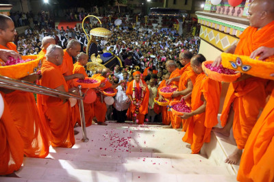 Awaiting sants lay flower petals at the feet of Acharya Swamishree Maharaj