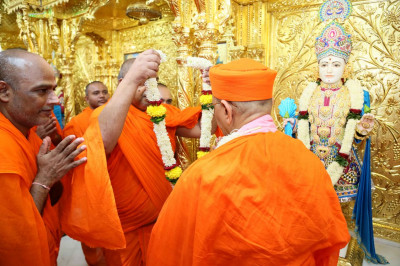 A garland is put on Acharya Swamishree Maharaj