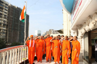 Acharya Swamishree, sants, and disciples salute the Tiranga