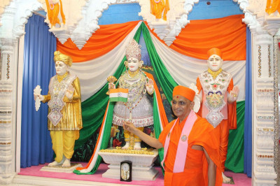 Acharya Swamishree waves a flag of India