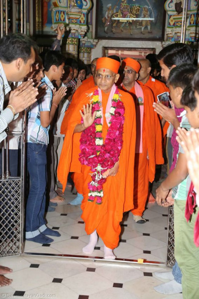 Acharya Swamishree gives darshan as He enter the Mandir