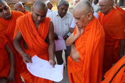 Acharya Swamishree Maharaj examines the floor plans