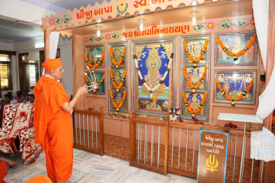 Acharya Swamishree Maharaj performs aarti to the Murtis