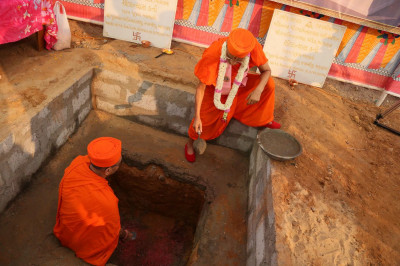 Acharya Swamishree Maharaj lays some mortar in the ground