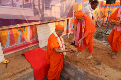 Acharya Swamishree Maharaj lays the bricks into the ground