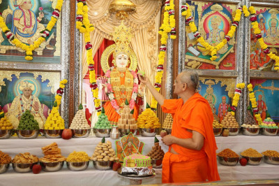 Prasad cake is offered to Lord Swaminarayan