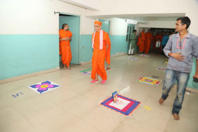 Acharya Swamishree Maharaj views the rangoli created by students of the Baal Mandir